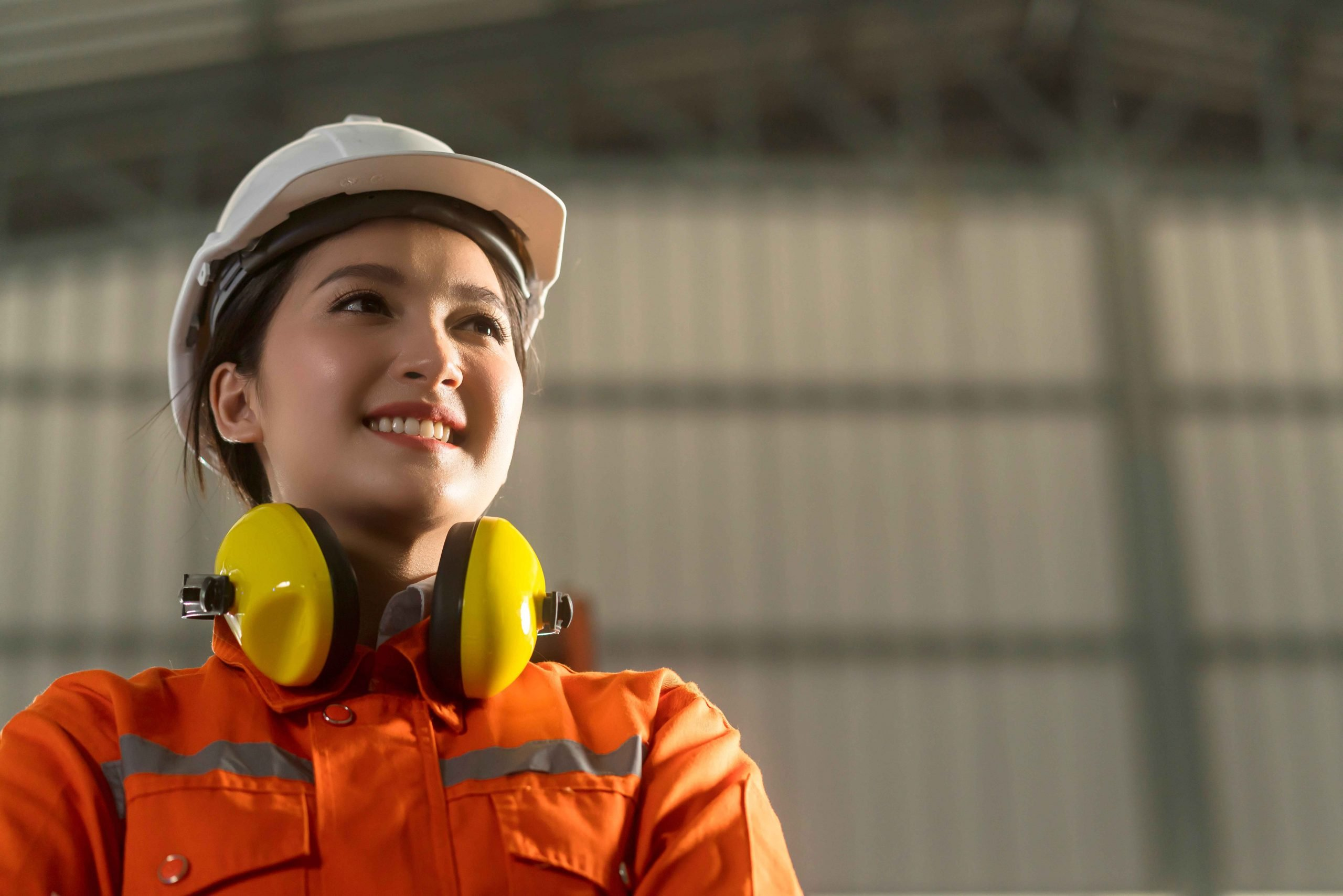 portrait of asian female engineer wearing uniform and saftey helmet standing confident and cheerful next to automation robot arm machine in factory background